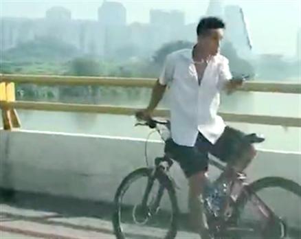 这位在东江大桥骑单车的老哥太厉害了,倒着骑车还耍双节棍