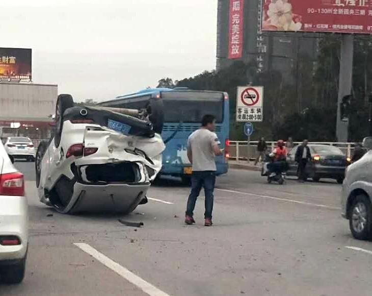 一小车被大巴车撞飞后,四脚朝天躺在路上