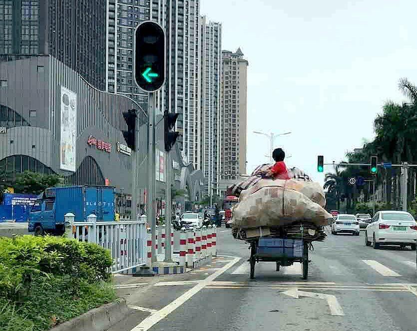 危险!陈江有人坐在载满货物的三轮车顶上