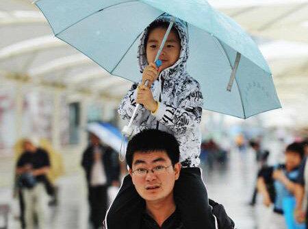 温情一幕!惠州一车主送伞给大雨里的父子